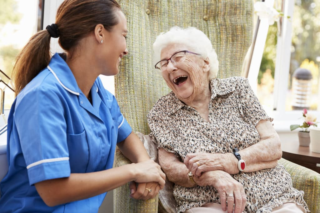 Senior Woman Sitting In Chair And Laughing With Nurse In Retirement Home (Personal Care at Home)